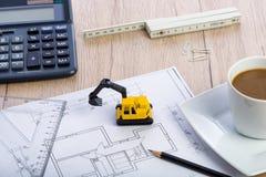 Desktop with blueprint yellow mini excavator, ruler and pencil Royalty Free Stock Photos