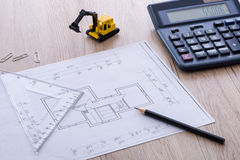 Desktop with blueprint yellow mini excavator, ruler and pencil Royalty Free Stock Image