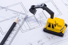 Desktop with blueprint yellow mini excavator, ruler and pencil Royalty Free Stock Photography