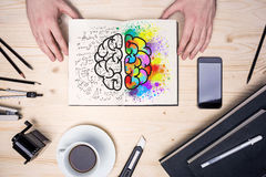 Desktop with brain sketch. Top view of wooden desktop with coffee cup, stationery items, smart phone and hands holding notepad with creative and analytical brain stock photography