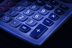 Desktop Calculator Keypad. Blue toned image of desktop calculator keypad. Black background Stock Photos