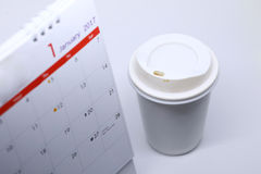Desktop calendar blank schedule of 1 january 2017 put on table. Work office with coffee cup Stock Images