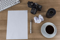 Desktop with camera blank sheet and coffee Royalty Free Stock Images