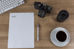 Desktop with camera blank sheet and coffee Royalty Free Stock Photo