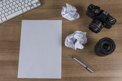 Desktop with camera and blank sheet Royalty Free Stock Photography