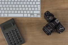 Desktop with camera keyboard and calculator Royalty Free Stock Photo