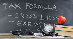 Desktop and chalkboard for learning how to do income taxes in cl Royalty Free Stock Photography