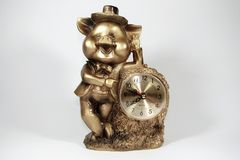 Desktop clock piggy. Golden table clock with statuette piggy standing at full height in a hat and a suit Royalty Free Stock Photography