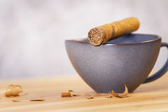 Desktop with coffee and cigar. Close up of wooden desktop with cigar on top of black coffee cup on blurry concrete background stock photos