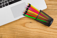 Desktop with colorful pencils on top of computer Royalty Free Stock Image