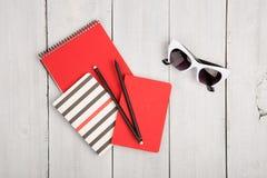 desktop com os blocos de notas do vermelho e da tira, pensils, óculos de sol em um wh imagens de stock royalty free