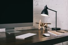 Desktop computer with blank screen and wooden plane model. At workplace stock image
