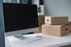 desktop computer con lo schermo in bianco e le scatole di cartone nel luogo di lavoro durante la rilocazione immagini stock
