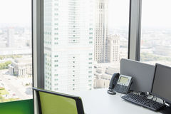 Desktop computer and landline phone on desk by glass window in office Stock Image