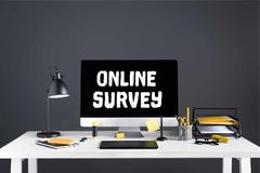desktop computer with online survey inscription on screen, graphics tablet and office supplies royalty free stock image