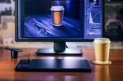 Desktop con il computer, la tavola dei grafici e una tazza di caffè fotografie stock libere da diritti