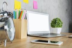 Desktop con il computer portatile bianco Fotografia Stock