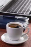 Desktop con la tazza di caffè, computer portatile aperto, Immagine Stock Libera da Diritti