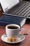Desktop con la tazza di caffè, il computer portatile aperto ed il diario, nessuna gente, messa a fuoco su caffè Immagine Stock Libera da Diritti