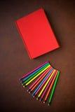 Desktop de madeira com lápis e o livro coloridos fotografia de stock