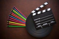 Desktop de madeira com placa de válvula colorida do lápis e do filme fotografia de stock
