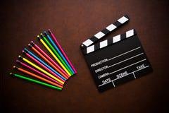 Desktop de madeira com placa de válvula colorida do lápis e do filme fotos de stock royalty free