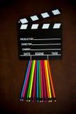 Desktop de madeira com placa de válvula colorida do lápis e do filme imagem de stock royalty free