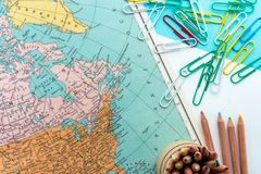Desktop design with map of Canada, Greenland and the North of America with colorful paperclips and colored pencils. Map of Canada, Greenland and the North of stock photos