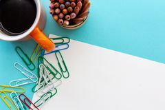 Free Desktop Design With Orange Mug Of Coffee, Colorful Paperclips And Colored Pencils Royalty Free Stock Photo - 152084435