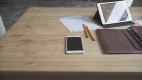 Desktop di legno marrone chiaro di area dell'area di lavoro della tavola con la tazza di caffè di cuoio dell'orologio del telefon video d archivio