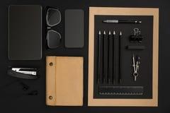 Desktop do escritório com vários objetos pretos no fundo Foto de Stock Royalty Free