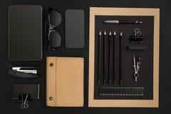 Desktop do escritório com vários objetos pretos no fundo Imagens de Stock