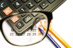 Desktop through the eyepiece on white background. Still life of calendar sheet calculator pencil and ruler viewed through the glasses eyepiece glasses Stock Photo
