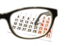 Desktop through the eyepiece on white background. Still life of a calendar sheet through the glasses eyepiece royalty free stock photos