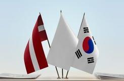 Flags of Latvia and South Korea. Desktop flags of Latvia and South Korea with white flag in the middle stock photos