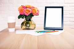 Desktop with frame and flowers. Front view of wooden desktop with roses, coffee cup, blank picture frame and colorful pencils on white brick wall background Stock Photo