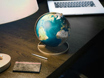 Desktop globe on the wooden table. Elements of this image furnished by NASA. 3d rendering. Desktop globe on the wooden table with lamp. Elements of this image Stock Image