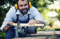 Worker beard man with circular saw. Desktop items, and the process of preparation of wood for sawing and construction Royalty Free Stock Photo