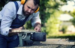 Worker beard man with circular saw. Desktop items, and the process of preparation of wood for sawing and construction Royalty Free Stock Images