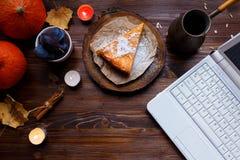 desktop Lap-top, πρόγευμα, cheesecake κολοκύθας, επιτραπέζιος λαμπτήρας, κολοκύθες, δαμάσκηνα σε έναν ξύλινο πίνακα στοκ εικόνες με δικαίωμα ελεύθερης χρήσης
