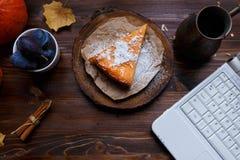 desktop Lap-top, πρόγευμα, cheesecake κολοκύθας, επιτραπέζιος λαμπτήρας, κολοκύθες, δαμάσκηνα σε έναν ξύλινο πίνακα στοκ φωτογραφία με δικαίωμα ελεύθερης χρήσης