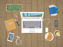 Desktop with laptop running the media player, personals, phone with messages, smart watch, headphones, notepad, tea, croissant. Royalty Free Stock Image