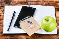 Desktop met document agenda, smartphone en groene appel stock afbeeldingen
