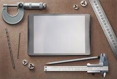 Desktop mit Bohrgeräten, Tablette, Tasterzirkel, Bleistift und anderem Stockbilder