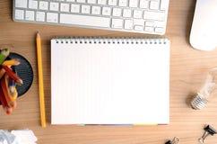 Desktop mit Papier, Briefpapier, Computer, leerem Notizblock und Glühlampe, Draufsicht lizenzfreie stockfotos