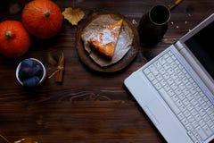 desktop Ordenador portátil, desayuno, pastel de queso de la calabaza, lámpara de mesa, calabazas, ciruelos en una tabla de madera foto de archivo libre de regalías