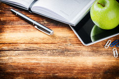 Desktop with paper agenda, digital tablet and green apple Royalty Free Stock Images