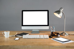 Desktop pc, digital tablet and table lamp with office accessories Stock Image