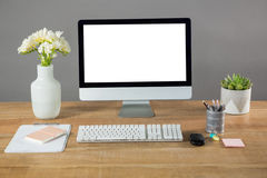 Desktop pc, flower vase and office stationery Royalty Free Stock Photos