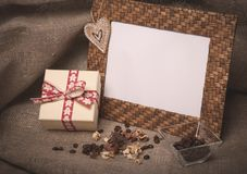 Desktop photo frame and coffee beans with gift box on linen Royalty Free Stock Images